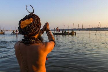 IBLFBD03151800 Sadhu, holy man, taking a bath and praying in the Sangam, the confluence of the rivers Ganges, Yamuna and Saraswati, just before sunset, Kumbha Mela mass Hindu pilgrimage, Allahabad, Uttar Pradesh, In...