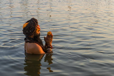 IBLFBD03151803 Sadhu, holy man, taking a bath and praying in the Sangam, the confluence of the rivers Ganges, Yamuna and Saraswati, just before sunset, Kumbha Mela mass Hindu pilgrimage, Allahabad, Uttar Pradesh, In...