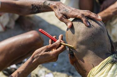 IBLFBD03152246 Pilgrim having his head shaved during Kumbha Mela, Allahabad, Uttar Pradesh, India