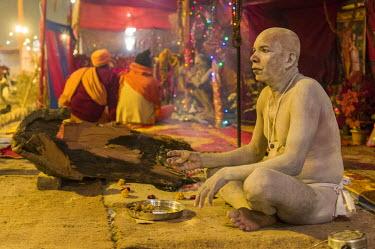 IBLFBD03152331 Shiva sadhu, holy man, sitting in his tent at the Sangam, the confluence of the rivers Ganges, Yamuna and Saraswati, during Kumbha Mela festival, Allahabad, Uttar Pradesh, India