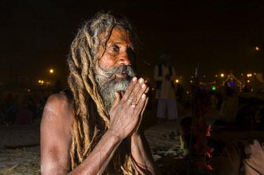 IBLFBD03152426 Shiva sadhu, holy man, sitting and praying at night at the Sangam, the confluence of the rivers Ganges, Yamuna and Saraswati, during Kumbha Mela festival, Allahabad, Uttar Pradesh, India