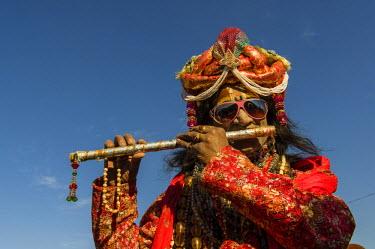 IBLFBD03152541 Colourfully costumed devotee playing flute during Kumbh Mela, Allahabad, Uttar Pradesh, India