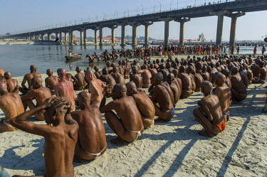 IBLFBD03152712 Sitting in silence at the river Ganges as part of the initiation of new sadhus, during Kumbha Mela festival, Allahabad, Uttar Pradesh, India