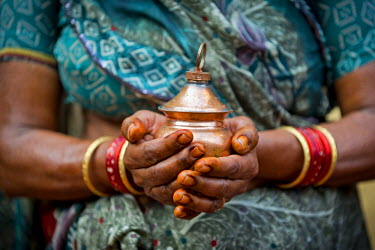 IBLOMK03667255 Hands of an Indian woman holding a vessel with holy water, Rameswaram, Pamban Island, Tamil Nadu, India