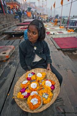 IBLOMK02295037 Girl selling leaf bowls with flowers and oil lamps for the Hindu Aarti ritual, Ghats, Ganges, Varanasi, Benares or Kashi, Uttar Pradesh, India