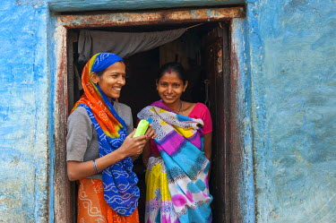 IBLOMK02295071 Two smiling women in a doorway, Varanasi, Benares or Kashi, Uttar Pradesh, India