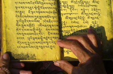 IBLFBD03095961 Tibetean monk reading the holy scriptures in Tibetan language, at the foot of Boudnath Stupa, Kathmandu Valley, Kathmandu, Kathmandu District, Bagmati Zone, Nepal