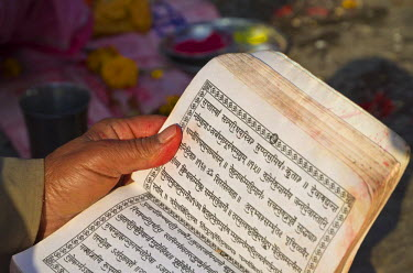 IBLFBD03099678 Devotee reading in the holy scriptures, written in Hindi characters, Kathmandu, Kathmandu District, Bagmati Zone, Nepal