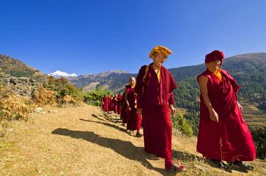 IBLFBD03113875 Monks and nuns wearing red cloths walking on a small path along a mountain slope, Junbesi, Solukhumbu District, Sagarmatha, Nepal