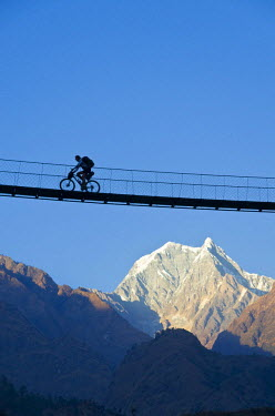 IBLFBD03134733 Cyclist crossing a suspension Bridge over Kali Ghandaki Valley, Nilgiri Mountain in the back, Tatopani, Annapurna Region, Nepal