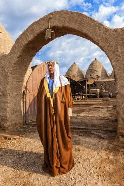 IBLGAB02346986 Turkish man wearing traditional cloth in his beehive adobe house, Harran, Sanliurfa province, Eastern Turkey