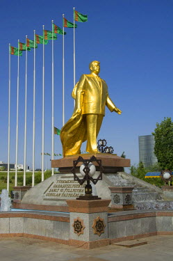 IBLGAB01111236 Gold covered statue of President Turkmenbasy in front of the monument of the 10th anniversary of Independence, Ashgabat, Turkmenistan
