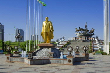 IBLGAB01111237 Gold covered statue of President Turkmenbasy in front of the monument of the 10th anniversary of Independence and Akhal-teke horses fountain, Ashgabat, Turkmenistan