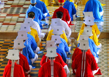 IBLGZS01204060 Monks and nuns, colorful robes in red, yellow, blue, praying, ceremonial midday prayer in the Cao Dai temple, Tay Ninh, Vietnam