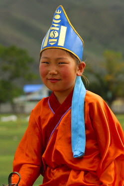 IBLGVA00791554 Ten-year-old girl wearing hat with soyombo emblem riding a horse, participant in the horsemanship competitions of the Naadam Festival, Mongolia