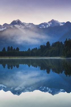 NZ02613 New Zealand, South Island, West Coast, Fox Glacier Village, Lake Matheson, reflection of Mt. Tasman and Mt. Cook, dawn