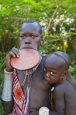 IBLGAB01735018 Surma woman with huge rounded lip plate and breastfeeding a baby, Kibish, Omo valley Valley, Ethiopia, Africa