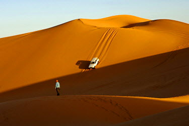 Off-road vehicle driving towards the sunset on a steep slope in the sand dunes of the Erg Muzuruq, Sahara, Libya, Africa