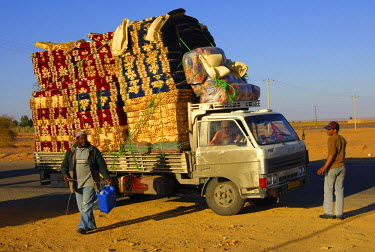 IBLGVA01756088 An overcharged pickup carrying colourful matrasses, Al Awaynat, Libya, North Africa, Africa