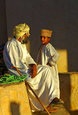 IBLGVA00762498 Father and son talking, wearing traditional Omani clothing, Nizwa, Oman, Middle East