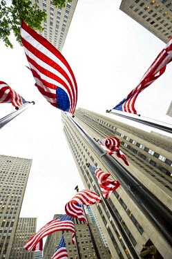IBLDJS02380438 Rockefeller Center with U.S. American flags, worm's-eye view, Manhattan, New York, USA