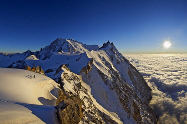 INT01128869 France, Alpinist on the aiguille du Midi (3848 m) to aiguille du Plan (3673 m) ridge in summer at sunset, Chamonix, Mont-Blanc range,