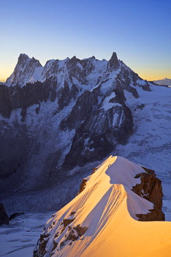 INT01128995 France, Alpinist on the aiguille du Midi (3848 m) to aiguille du Plan (3673 m) ridge in summer at sunrise, Chamonix, Mont-Blanc range,