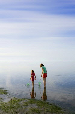 IBLDJS03046012 Woman and girl with dip nets standing in the Wadden Sea, Wyk, Fohr, Schleswig-Holstein, Germany