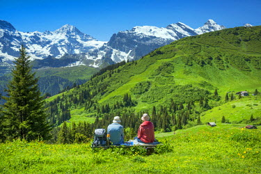 SWI7818AW Europe, Switzerland, Bern, Bernese Oberland,  people sitting on bench looking towards the Alps