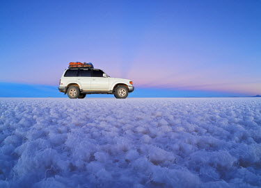 BOL8530AW Bolivia, Potosi Department, Daniel Campos Province, White Toyota Landcruiser on the Salar de Uyuni, the largest salt flat in the world at sunset.