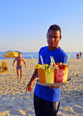 BRA3141AW Brazil, City of Rio de Janeiro, Man selling caipirinha on Ipanema Beach.