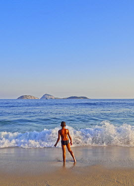 BRA3142AW Brazil, City of Rio de Janeiro, Boy and waves at Ipanema.