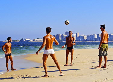 BRA3159AW Brazil, City of Rio de Janeiro, Group of people playing football on Copacabana Beach.