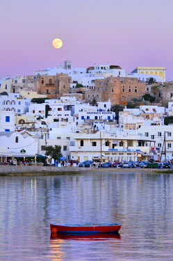 IBXGZS00898006 Red wooden boat in the sea in front of white houses, full moon in the pink evening sky over Naxos City with Castro, Venetian fortress, Cyclades, Greece