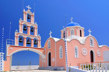 IBXGZS00903383 Bell tower with six bells and a pink and light blue Greek church Karterados, Santorini, Cyclades, Greece