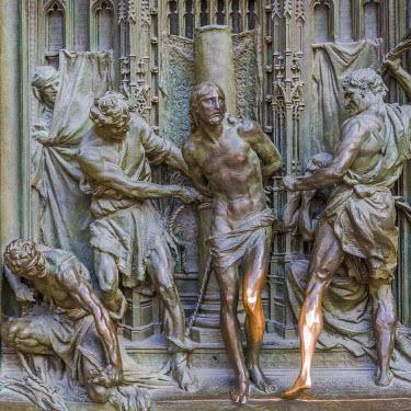 IBXMRA04337578 Bronze sculptures at the entrance portal of Milan Cathedral, Piazza del Duomo, Milan, Italy