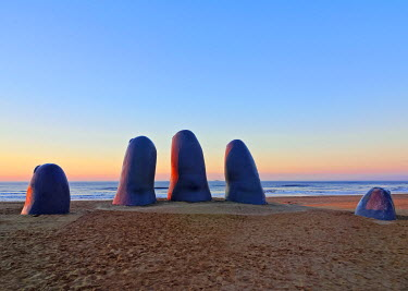 URU0275AW Uruguay, Maldonado Department, Punta del Este, Playa Brava, La Mano(The Hand), a sculpture by Chilean artist Mario Irarrazabal at sunrise.