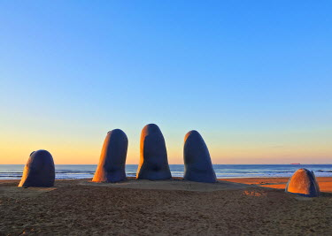 URU0322AWRF Uruguay, Maldonado Department, Punta del Este, Playa Brava, La Mano(The Hand), a sculpture by Chilean artist Mario Irarrazabal at sunrise.
