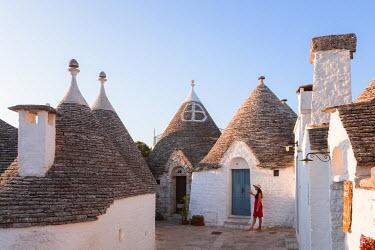 ITA9284AW Woman visiting the Trulli area, Alberobello, Itria valley, Apulia, Italy  (MR)