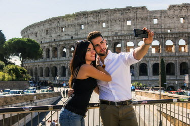 ITA9418AW Young caucasian couple taking a selfie with a smartphone in front of the Colosseum, Rome, Lazio, Italy (MR)