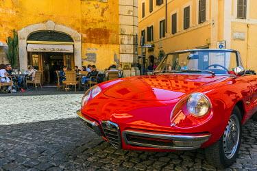 ITA9423AW Alfa Romeo Duetto spider parked in a cobblestone street of Rome, Lazio, Italy