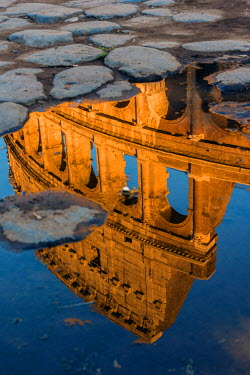 ITA9426AW Colosseum or Coliseum reflected in a puddle at sunset, Rome, Lazio, Italy