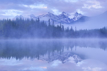 CAN3037AW Snow capped mountains reflect in a misty Herbert Lake, Canadian Rockies, Banff National Park, Alberta, Canada. Autumn (September) 2016.