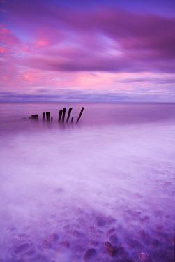 ENG13522AW Wooden posts at high tide on Porlock Beach, Exmoor, Somerset.