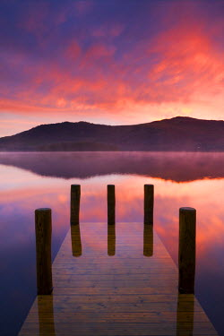 ENG13582AW Fiery sunrise over Derwent Water from Hawes End jetty, Lake District National Park, Cumbria, England. Autumn (November) 2009