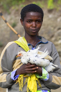 AF16EGO0011 Africa, Ethiopian Highlands, Eastern Amhara, Lalibela. Young woman returning from the market with a chicken.