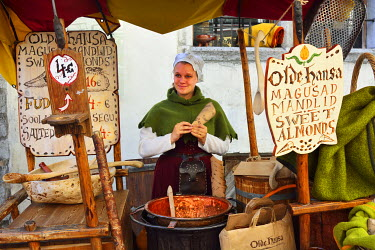 EST1213AW Girl selling almonds in a medieval street. Old Town of Tallinn, a Unesco World Heritage Site. Tallinn, Estonia