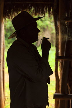 CA11BTH0038 Cuba, Vinales. Silhouette of a tobacco farmer smoking a cigar.