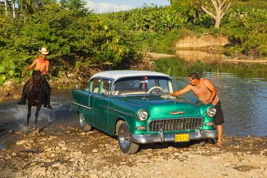 CA11BTH0055 Cuba. Horseback rider runs past a man washing his classic American car in the Gurabo river outside Trinidad.