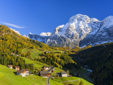 Traditional mountain farms clustered in hamlets called Viles in Gader Valley, Val Badia in the Dolomites of South Tyrol, Alto Adige. Mountain Range Kreuzkofelgruppe, Sasso Santa Croce in the backgroun...